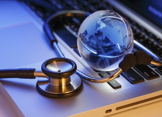 Stethoscope and globe on a laptop keyboard, focus on stethoscope